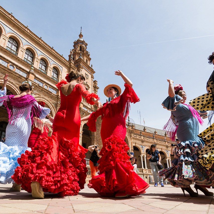 Seville, Spain - May 2017: Young women dance flamenco on Plaza de Espana during famous Feria festival