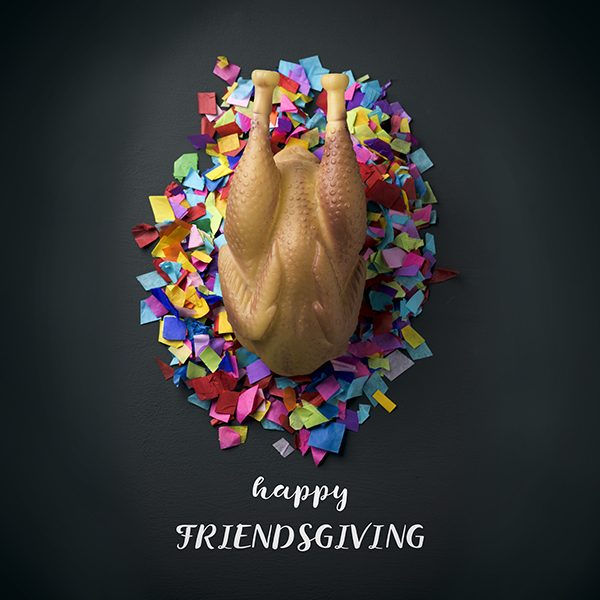 high-angle shot of a rubber roast turkey on a pile of confetti, placed on a rustic surface, and the text happy friendsgiving